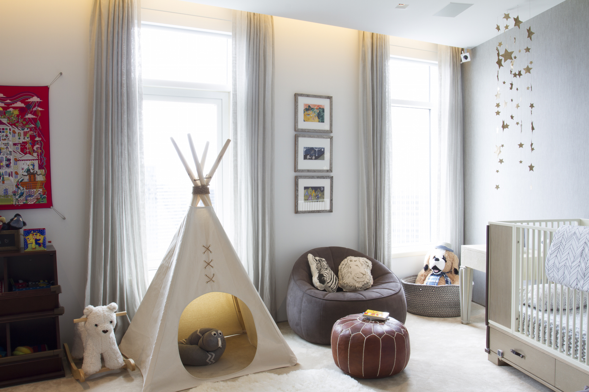 A playful baby boy nursery complete with teepee, stuffed animals & creative shelving. Designed by Havenly.