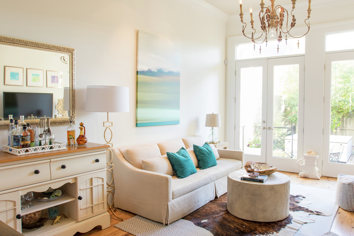 bright and airy new orleans living room with cowhide rug and blue pillows