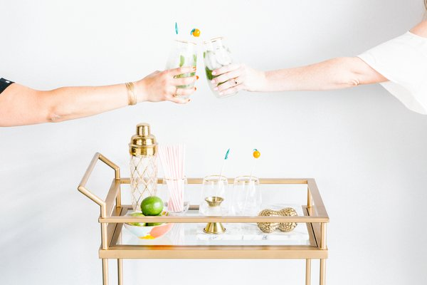 Hands Cheersing over a bar cart